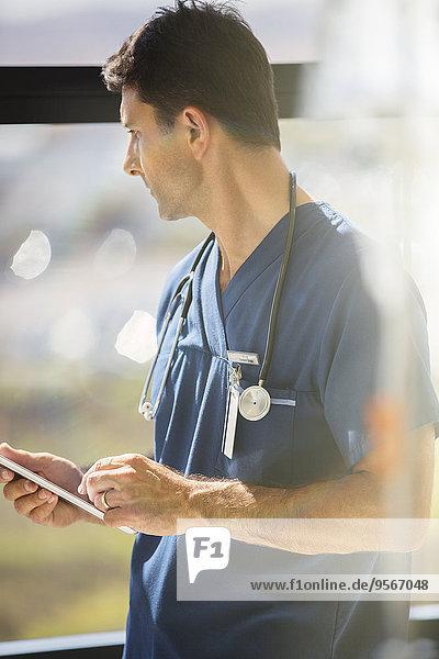 Männlicher Arzt mit Tabletten-PC und Blick aus dem Krankenhausfenster