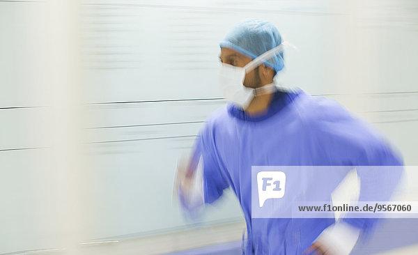 Männlicher Chirurg stürmt durch den Krankenhausflur