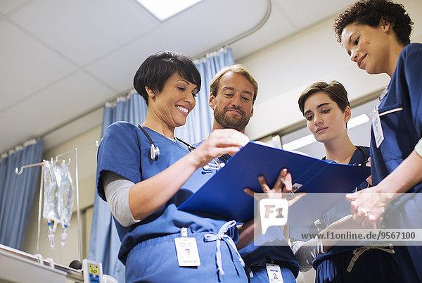Ärzte in Kittel  die sich Dokumente in der Krankenstation ansehen.
