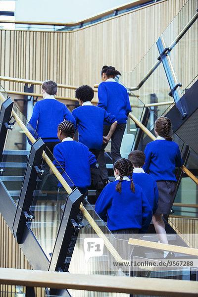 Rückansicht einer Gruppe von Schülern in blauen Schuluniformen  die in der Schule die Treppe hinaufgehen.