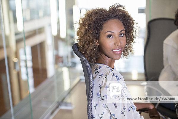Porträt einer jungen Geschäftsfrau  die auf dem Stuhl sitzt und in die Kamera schaut.