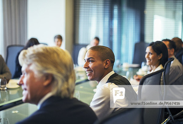 Smiling businessman attending business meeting in conference room