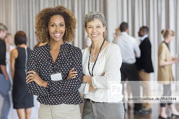 Geschäftsfrauen posieren vor Kollegen im Büro