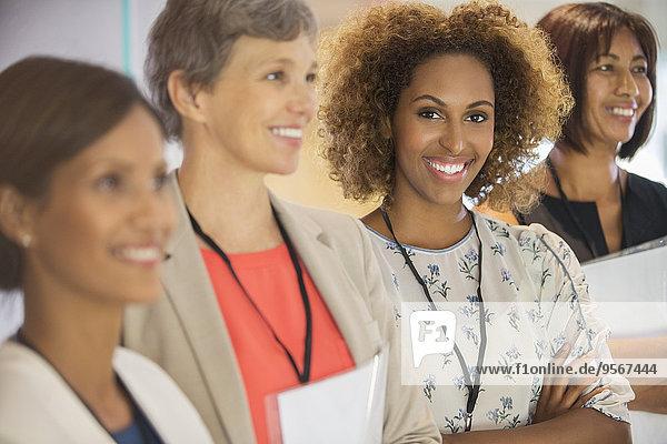 Porträt einer Geschäftsfrau  die in die Kamera schaut und mit ihren Kollegen steht.