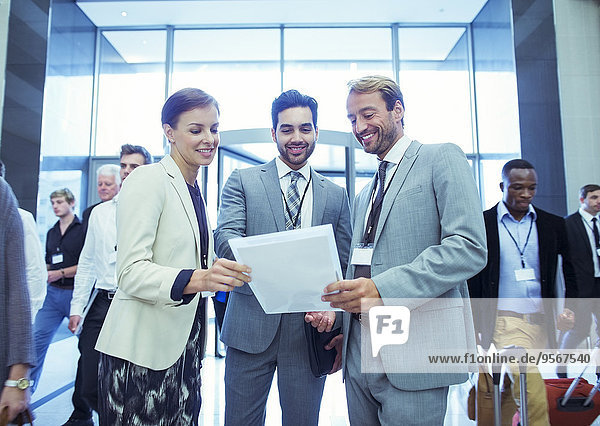 Porträt einer Geschäftsfrau und zweier Geschäftsleute  die in der Lobby des Konferenzzentrums stehen.