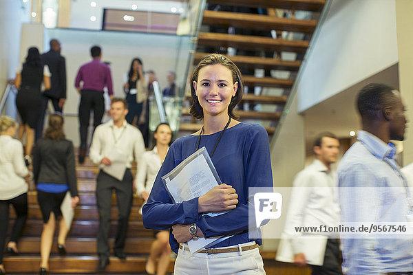 Porträt einer lächelnden jungen Frau  die in der Lobby des Konferenzzentrums steht.