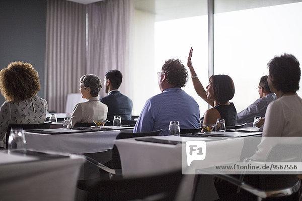 Mittlere Gruppe von Konferenzteilnehmern  die im Konferenzraum sitzen und die Hand heben.