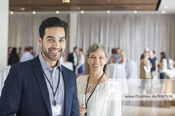 Porträt eines Mannes und einer Frau  die in der Lobby des Konferenzzentrums stehen  lächelnd