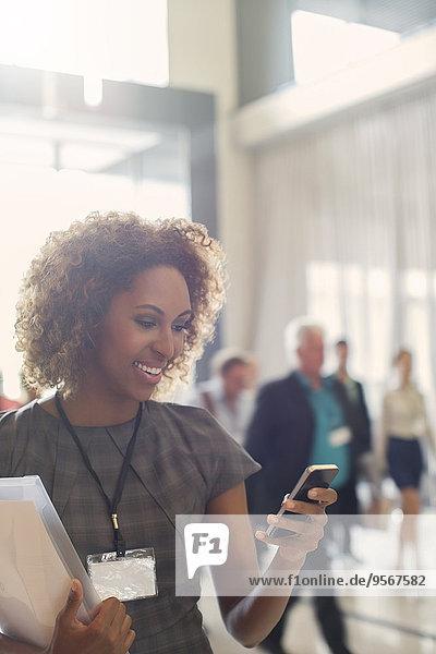Portrait einer lächelnden jungen Frau  die in der Lobby des Konferenzzentrums steht  mit dem Smartphone.