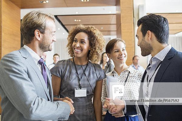 Vier Geschäftsleute schütteln sich zu Beginn des Treffens die Hand