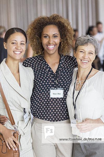 Porträt von drei Frauen  die in der Sitzungspause vor der Kamera lächeln