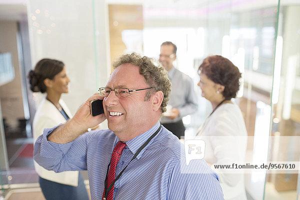 Geschäftsmann im Gespräch am Handy  Kollegen im Hintergrund