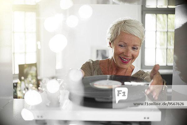 Ältere Frau spielt Schallplatte auf Plattenteller