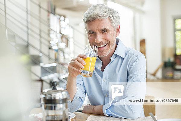 Älterer Mann trinkt Orangensaft am Frühstückstisch