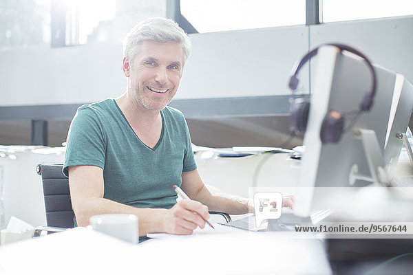 Älterer Mann bei der Arbeit am Computer am Schreibtisch