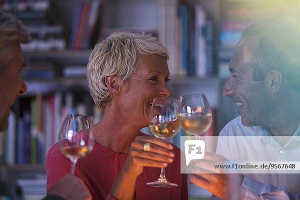 Ältere Freunde stoßen sich mit Weißwein an.