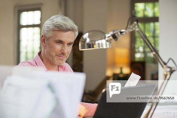 Älterer Mann mit Laptop im Home-Office
