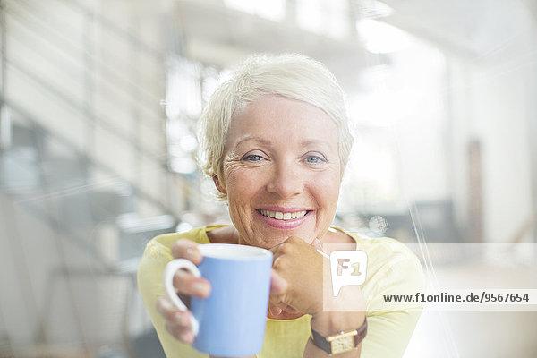 Ältere Frau trinkt eine Tasse Kaffee