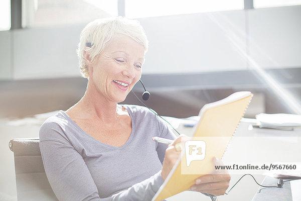 Geschäftsfrau in Headset-Schrift auf Notizblock im Büro