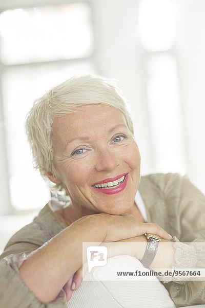 Ältere Frau lächelt auf dem Sofa