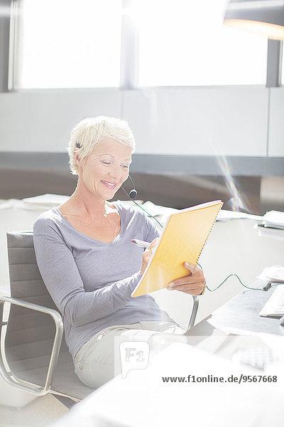 Geschäftsfrau im Headset Schreiben im Notebook am Schreibtisch