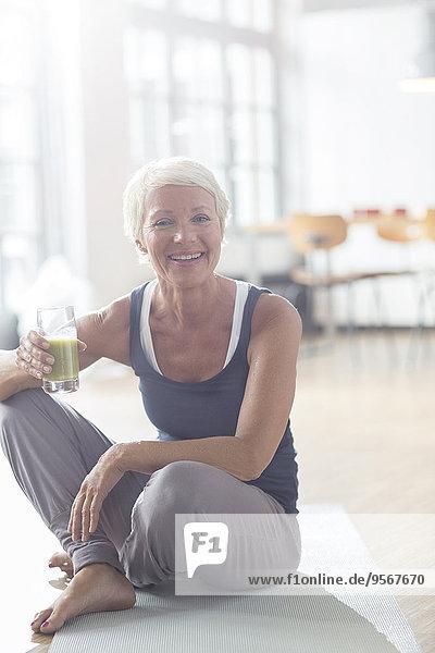 Ältere Frau trinkt Saft auf Trainingsmatte