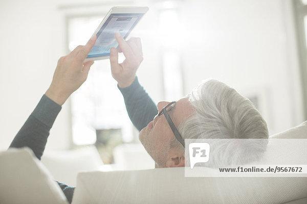 Älterer Mann mit digitalem Tablett im Wohnzimmer