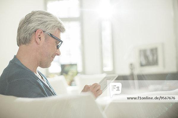 Älterer Mann mit digitalem Tablett auf dem Sofa