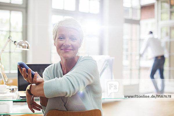 Geschäftsfrau mit Handy am Schreibtisch zu Hause
