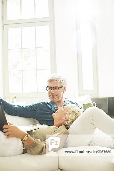 Älteres Paar entspannt sich gemeinsam auf dem Wohnzimmersofa