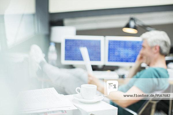 Geschäftsmann liest Papierkram im Büro hinter der Kaffeetasse