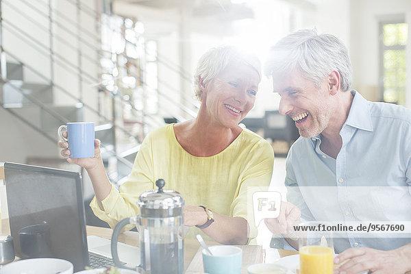 Älteres Paar lacht gemeinsam am Frühstückstisch mit Laptop