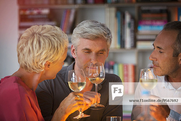 Ältere Freunde bei der Verkostung von Weißwein