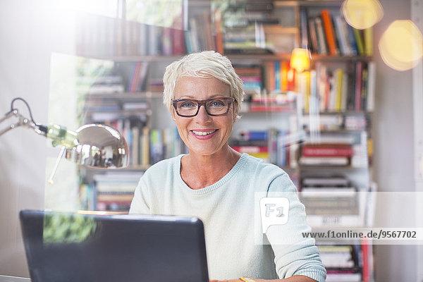 Geschäftsfrau lächelt am Computer im Home-Office