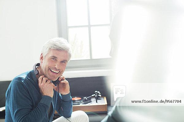 Älterer Mann hört Plattenspieler mit Kopfhörer