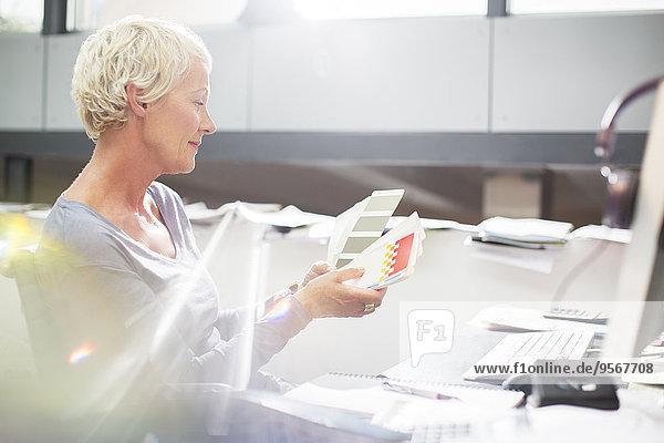Geschäftsfrau beim Prüfen von Farbmustern am Schreibtisch