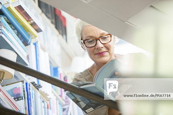 Niederwinkelansicht der älteren Frau beim Lesen des Buches