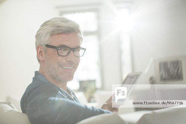 Älterer Mann mit digitalem Tablett auf dem Wohnzimmersofa