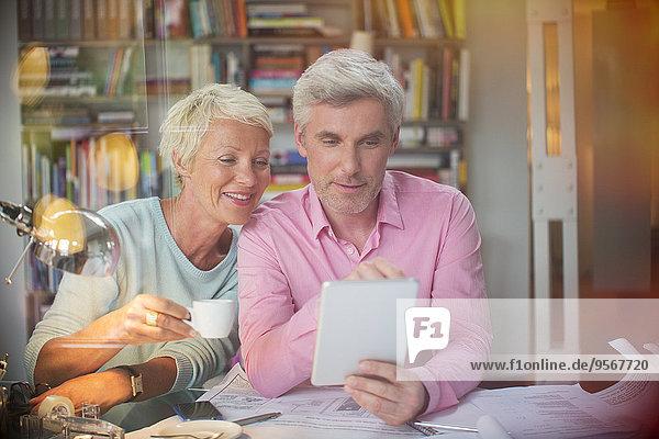Geschäftsleute  die ein digitales Tablett im Home-Office verwenden