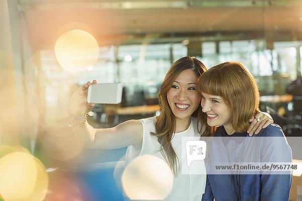 Geschäftsfrauen nehmen Handy-Selfie im Büro mit