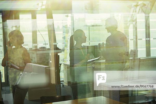 Silhouette von Geschäftsleuten  die im Büro reden
