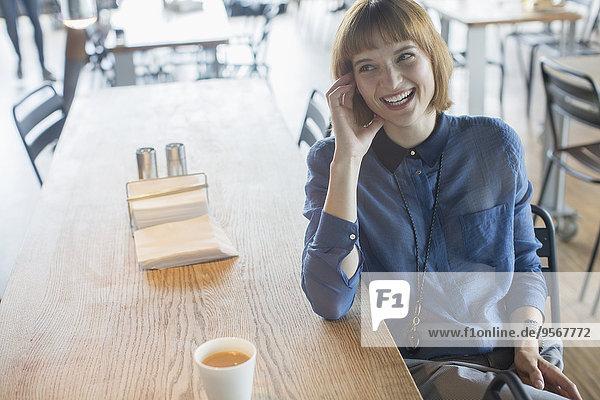 Geschäftsfrau lacht am Cafeteria-Tisch