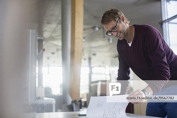 Geschäftsmann beim Lesen von Papierkram im Büro