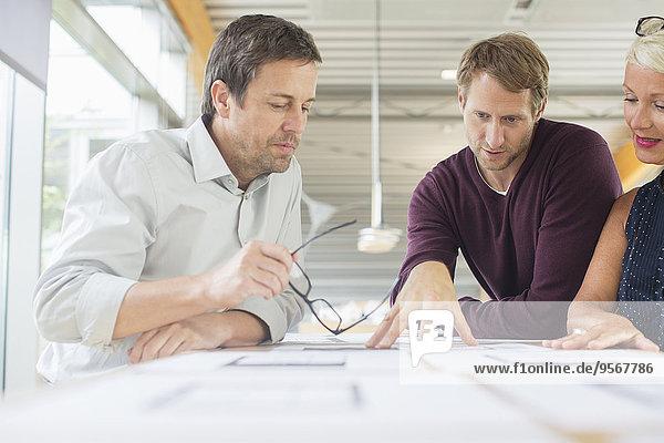 Geschäftsleute beim Lesen von Papierkram im Büromeeting