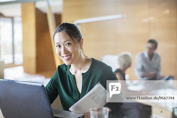 Geschäftsfrau lächelt mit Laptop im Büro