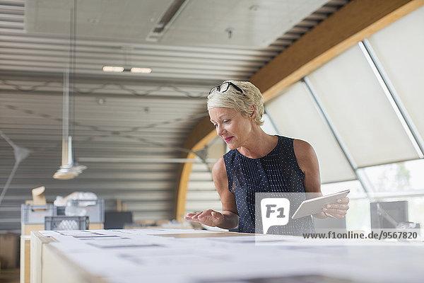 Geschäftsfrau beim Lesen von Papierkram im Büro