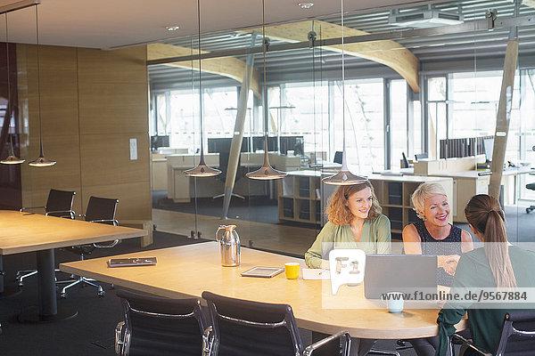 Geschäftsfrauen schütteln sich in Bürobesprechung die Hand