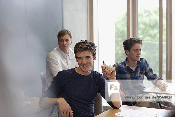 Porträt eines lächelnden Studenten am Schreibtisch