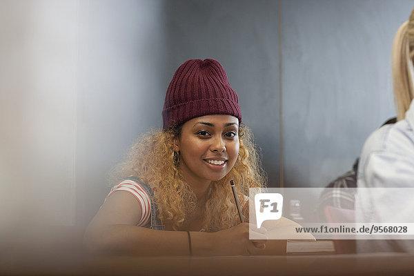 Porträt einer lächelnden Studentin beim Schreiben von Notizen im Unterricht