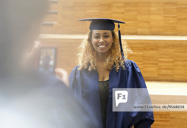 Studentin im Promotionskleid posiert für Bild im Flur der Universität
